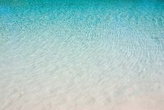 El agua azul ondula la arena blanca Fotos de archivo
