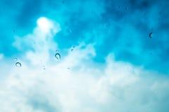 El agua cae el fondo Riegue los descensos en la ventana de cristal sobre SK azul Imágenes de archivo libres de regalías
