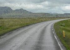 El agua cae en la ventanilla del coche después de la lluvia con el camino solo entre las montañas en un fondo, Islandia del sur,  foto de archivo libre de regalías