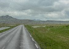 El agua cae en la ventanilla del coche después de la lluvia con el camino solo entre las montañas y el glaciar en un fondo, Islan imágenes de archivo libres de regalías