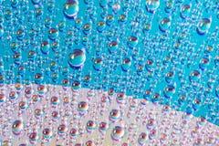 El agua cae en los medios del DVD, descensos del agua en fondo colorido imagenes de archivo