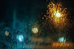 El agua cae sobre el vidrio del lado del coche en oscuridad foto de archivo