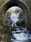El agua cae a través de arco Imagenes de archivo