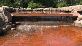 El agua clara llena una fuente de la parte inferior roja de tierra almacen de metraje de vídeo