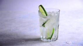 El agua con hielo y cal de las rebanadas vierte en el vidrio C?mara lenta Refresque la bebida del verano almacen de video