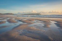 El agua crea arroyuelos mientras que una onda corre retrocede la playa imagenes de archivo