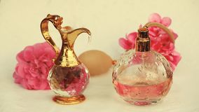 El agua de botella de cristal de perfume cae el hd de las flores del jarro del oro almacen de video