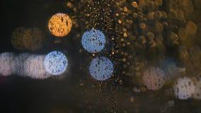 El agua de lluvia cae en el vidrio de la ventana del autobús en día lluvioso con tráfico de ciudad borroso de la noche como fondo almacen de video