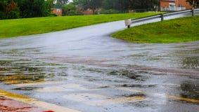 El agua de lluvia del camino cae el fondo con la reflexión del cielo azul y círculos en el asfalto oscuro pronóstico Imágenes de archivo libres de regalías