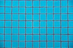 El agua del claro de la piscina que muestra las tejas del cuadrado de la arcilla de los azules turquesa y el cemento gris mampost Imagen de archivo libre de regalías