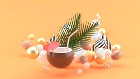 El agua del coco y el coco están entre las bolas coloridas en el fondo anaranjado foto de archivo