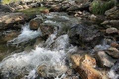 El agua del río de la montaña fluye abajo de las rocas Fotografía de archivo