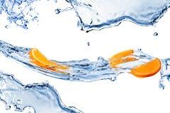 El agua dulce salpica y las rebanadas anaranjadas aisladas en blanco Imágenes de archivo libres de regalías