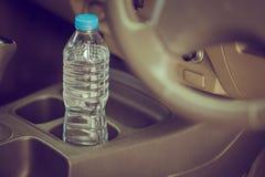 El agua embotellada del concepto de la imagen fue dejada en el coche durante mucho tiempo ¿Para beberlo? Foto de archivo libre de regalías