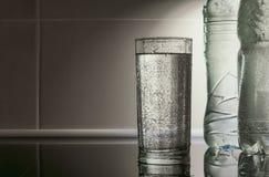 El agua en el cubilete en un fondo de rayos ligeros fotografía de archivo