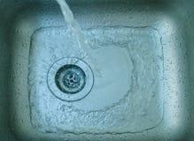 El agua en el fregadero Imagenes de archivo