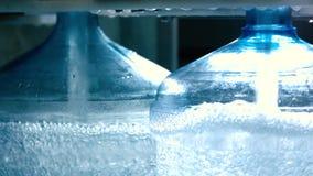 El agua está llenando encima de las botellas almacen de video