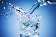 El agua está vertiendo en el vidrio en fondo azul Fotografía de archivo libre de regalías
