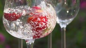 El agua está vertiendo en un vidrio con las fresas almacen de video