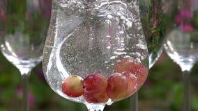 El agua está vertiendo en un vidrio con las uvas metrajes