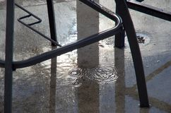 El agua gotea debajo de los muebles en un patio después de que un chubasco de la lluvia como el sol se rompa a través fotografía de archivo libre de regalías