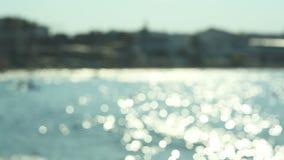 El agua ondulada fresca chispeante es brillante en un día de verano soleado, resume el fondo borroso en la playa almacen de video