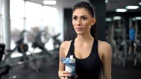 El agua potable después del entrenamiento del gimnasio, aguamarina de la señora apta equilibra, nutrición sana fotos de archivo libres de regalías