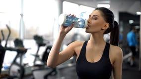 El agua potable después del entrenamiento del gimnasio, aguamarina de la señora del deporte equilibra, nutrición sana foto de archivo libre de regalías