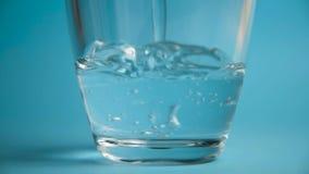 El agua pura se vierte en un vidrio transparente de cristal almacen de metraje de vídeo