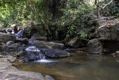 El agua que fluye sobre rocas y árboles abajo de una cascada en la cascada de Khao Ito, Prachin Buri en Tailandia imagen de archivo