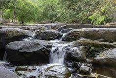 El agua que fluye sobre rocas y árboles abajo de una cascada en la cascada de Khao Ito, Prachin Buri en Tailandia foto de archivo libre de regalías