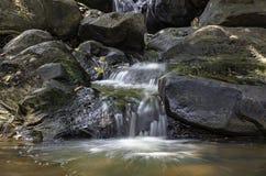 El agua que fluye sobre rocas y árboles abajo de una cascada en la cascada de Khao Ito, Prachin Buri en Tailandia fotografía de archivo libre de regalías