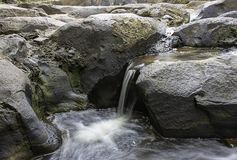 El agua que fluye sobre rocas y ?rboles abajo de una cascada en la cascada de Khao Ito, Prachin Buri en Tailandia imagen de archivo libre de regalías
