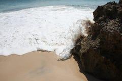 El agua que hace espuma golpea la roca Fotografía de archivo