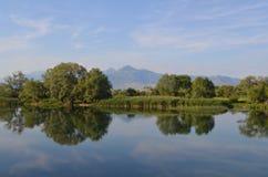 El agua reservada de un lago permite reflexiones de espejo hermosas el día soleado Panorama asombroso del paisaje de la naturalez fotos de archivo