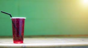 El agua roja en un vidrio plástico tiene un tubo del lechón, tiene un fondo y es soleada Fotografía de archivo libre de regalías