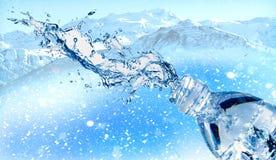 El agua salpica de la botella de agua plástica, montaña nevosa hermosa en la tierra trasera fotografía de archivo libre de regalías
