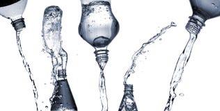 El agua salpica de las botellas Imagenes de archivo
