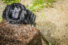 El agua salpica en un reloj rugoso Imágenes de archivo libres de regalías