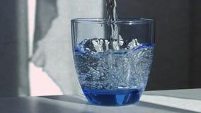 El agua se vierte en un cubilete de cristal almacen de metraje de vídeo