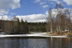 El agua tranquila en un pequeño lago con alguno hiela a la izquierda Foto de archivo