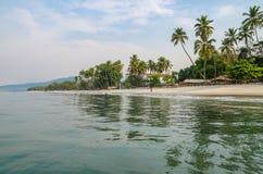 El agua tranquila, las palmeras y la arena blanca varan en la playa de Tokeh, al sur de Freetown, Sierra Leone, África Imagen de archivo libre de regalías