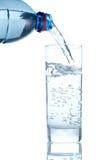 El agua vertió de la botella al vidrio Foto de archivo libre de regalías
