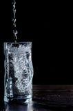 El agua vertió en el vidrio en fondo negro Foto de archivo libre de regalías