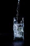 El agua vertió en el vidrio en fondo negro Fotografía de archivo libre de regalías