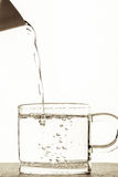 El agua vertió en un vidrio Fotografía de archivo libre de regalías