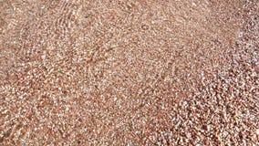 El agua vierte la arena de la playa almacen de video