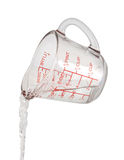 El agua vierte la taza de medición Foto de archivo