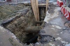 El agujero grande en el camino hecho para el camino que repara trabajos con cautela firma Imagen de archivo libre de regalías