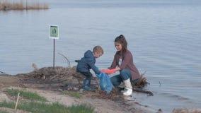 El ahorro ambiental, muchacho del niño ayuda al terraplén para arriba contaminado limpio del río del activista voluntario de la m metrajes
